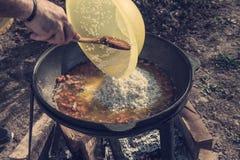 Le mani hanno messo il riso in un grande calderone per la cottura del pilaf all'aperto un giorno soleggiato immagini stock libere da diritti