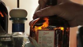 Le mani hanno messo la bottiglia di whiskey sullo scaffale della barra stock footage