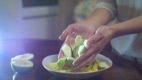 Le mani hanno messo le fette di mela su un piatto prima di cuocere video d archivio