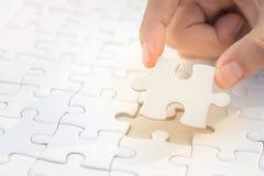 Le mani hanno messo puzzle dei pezzi di puzzle l'ultimo, concetto di affari per Fotografia Stock