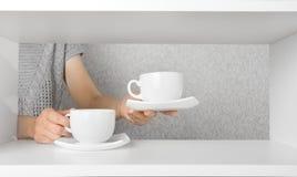 Le mani hanno messo sopra le tazze dello scaffale con i piattini Fotografia Stock