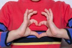 le mani hanno piegato sotto forma di un cuore contro fotografia stock