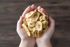 Le mani hanno riempito di banane secche su un fondo scuro immagini stock libere da diritti