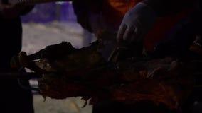 Le mani hanno tagliato i pezzi di carne arrostita dalla carcassa di maiale alla notte al rallentatore archivi video