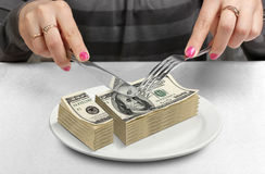 Le mani hanno tagliato i soldi sul piatto, riducono il concetto dei fondi immagini stock