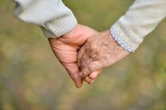 Le mani hanno tenuto insieme su un primo piano verde naturale del fondo fotografia stock libera da diritti