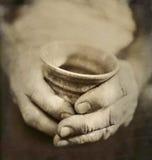 Le mani indossate dell'uomo che tengono tazza ceramica giapponese incrinata Fotografia Stock