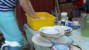 Le mani lavano i piatti sporchi sulla tavola all'aperto del villaggio rurale stock footage