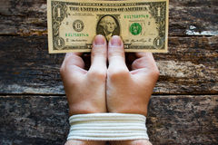 Le mani limitano gli uomini ed i soldi nelle mani un simbolo di schiavitù Fotografia Stock
