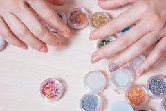 Le mani Manicured della donna con le decorazioni per i chiodi progettano Immagine Stock Libera da Diritti