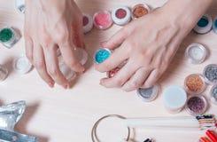 Le mani Manicured della donna prepeared funzionano con le decorazioni per progettazione dei chiodi Immagine Stock