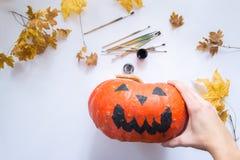 Le mani maschii decorano una zucca di Halloween su un fondo bianco Immagini Stock Libere da Diritti