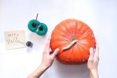 Le mani maschii decorano una zucca di Halloween su un fondo bianco Immagini Stock