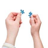 Le mani maschii e femminili con poco puzzle collega Immagini Stock