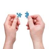 Le mani maschii e femminili con poco puzzle collega Fotografia Stock