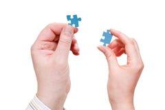 Le mani maschii e femminili con poco puzzle collega Immagine Stock