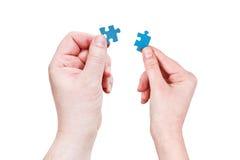 Le mani maschii e femminili con poco puzzle collega Fotografie Stock