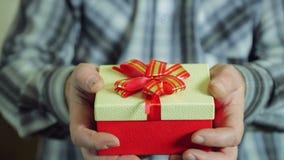 Le mani maschii estraggono da dietro la scatola con un regalo di Natale stock footage