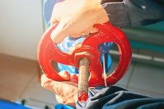 Le mani maschii girano la valvola rossa nel locale caldaie fotografie stock libere da diritti