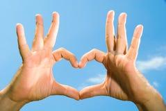 Le mani maschii hanno piegato sotto forma del cuore Fotografia Stock