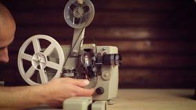Le mani maschii includono un vecchio proiettore di film archivi video