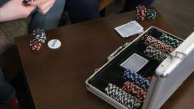 Le mani maschii prendono le carte ed i chip dalla cassa della mazza sulla tavola fotografia stock libera da diritti