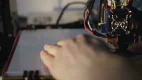 Le mani maschii prendono un distintivo stampato sulla stampante 3D HD pieno stock footage