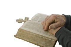 Le mani maschii si sono chiuse nella preghiera su una bibbia aperta Immagini Stock