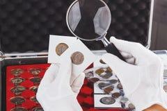 Le mani nei guanti tengono le monete del collettore dell'oro e della lente d'ingrandimento nelle vibrazioni Fotografia Stock