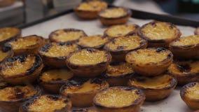 Le mani portoghesi tradizionali dell'uovo prendono i dolci pastosi acidi, il dessert Pasteis de nata con pasticceria portoghese d stock footage