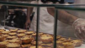 Le mani portoghesi tradizionali dell'uovo prendono i dolci pastosi acidi, il dessert Pasteis de nata con pasticceria portoghese d archivi video