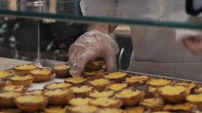 Le mani portoghesi tradizionali dell'uovo prendono i dolci pastosi acidi, il dessert Pasteis de nata con pasticceria portoghese d video d archivio