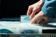 Le mani prendono il CD dalla valigia del metallo in pieno del CD di pirateria di musica e di film che vende illegalmente sul merc Immagini Stock