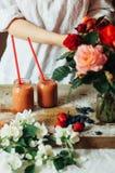 Le mani produce i frullati della fragola in tavola di legno Strawbe fresco Immagine Stock