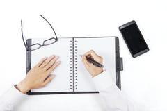 Le mani redigono una lista sull'ordine del giorno personale Fotografia Stock