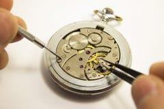 Le mani riparano un vecchio orologio Immagine Stock Libera da Diritti