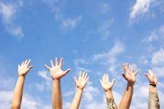 Le mani rised in su in aria attraverso il cielo Fotografia Stock
