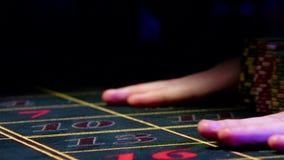 Le mani scommettevano i chip, uno cadono giù sulla tavola delle roulette, nera stock footage