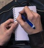 Le mani scrivono una lettera A disposizione una penna per scrivere immagini stock