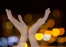 Le mani si aprono a forma di v con il fondo leggero scintillante del bokeh Fotografia Stock Libera da Diritti