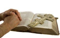 Le mani si sono chiuse nella preghiera e nella traversa Immagine Stock
