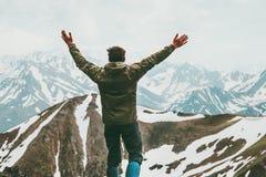 Le mani sollevate uomo felice dell'avventuriere sulla sommità viaggiano immagine stock