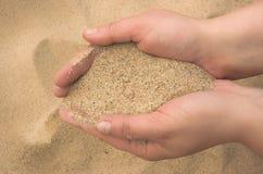 Le mani spargono la sabbia Fotografie Stock