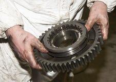 Le mani sporche del meccanico tiene un grande ingranaggio Fotografia Stock