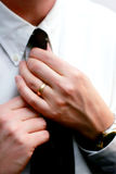 Le mani sposate raddrizzano una cravatta Immagini Stock