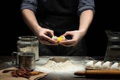 Le mani stanno rompendo un uovo in farina per produrre la pasta fotografia stock libera da diritti