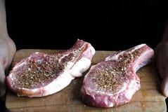 le mani stanno tenendo un bordo su cui sono due bistecche crude della carne di maiale spruzzate con le spezie e pronte da cucinar fotografie stock