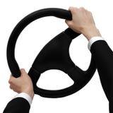 Le mani su un volante si girano verso la parte di sinistra Fotografie Stock