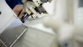 Le mani su una macchina verticale fa una cucitura laterale su una fabbrica del materasso archivi video