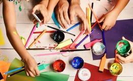 Le mani tengono gli indicatori variopinti, le matite e le pitture Rifornimenti di arte in mani maschii e femminili su fondo bianc fotografia stock